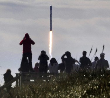 Visitors watch a Falcon 9 SpaceX rocket with a payload of approximately 60 satellites for SpaceX's Starlink broadband network lift off last year.