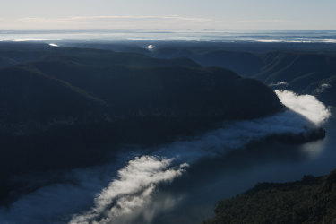 Lake Burragorang, partly shrouded in cloud, sits behind Warragamba Dam. It went from 42 per cent full to spilling within four months, with most of the increase coming from a single rain event in February.
