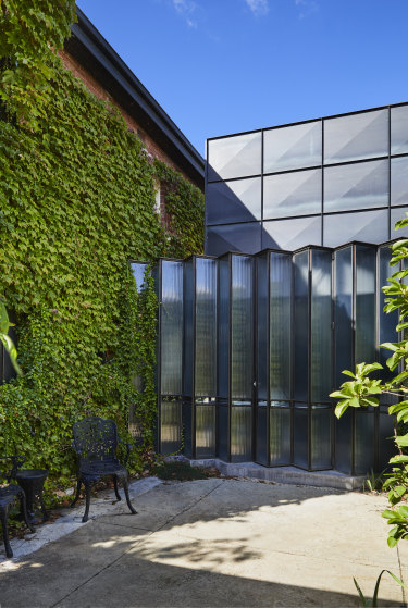 The striking extension of steel and fluted glass creates a dramatic juxtaposition to the original 1930s brick building and its cladding of Boston ivy.