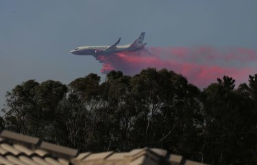 Water bombing aircraft works to save homes at Greta.