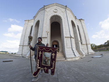 A man carries out a banner from the Holy Saviour Cathedral damaged by shelling during a military conflict, in Shushi, in the self-proclaimed Republic of Nagorno-Karabakh.