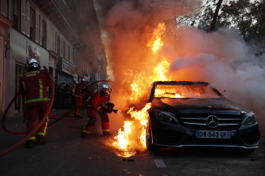 Firefighters pull out a fire on a burning car during a protest in Paris.