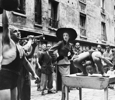 Elise Daniels with street performers, suit by Balenciaga, Le Marais, Paris, 1948.