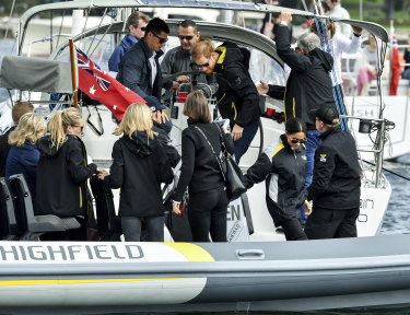Getting cramped.  Prince Harry, centre top, and his wife Meghan, second from right, sail on Sydney Harbour during the Invictus Games last Sunday.