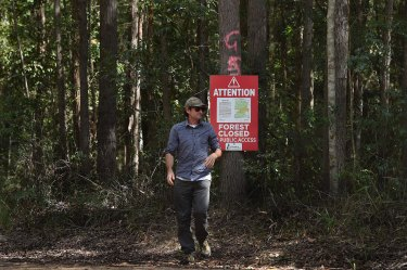 Mark Graham, an ecologist from Bellingen Nature Tours, near a sign stating the Lower Bucca State Forest is closed. Logging operations were still going in mid-September.
