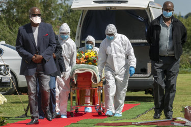 Pallbearers wearing personal protective equipment suits carrying the casket containing the remains of a COVID-19 victim in Johannesburg, South Africa.