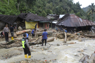 Rescuers search for victims following a flash flood in Mandailing Natal district.