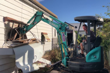 Malcolm Taylor uses an excavator to damage his late mother's house in Murtoa.