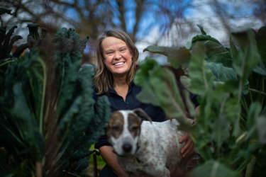 Gardening Australia host Millie Ross and her dog, Squid, in the midst of some leafy greens in her garden.