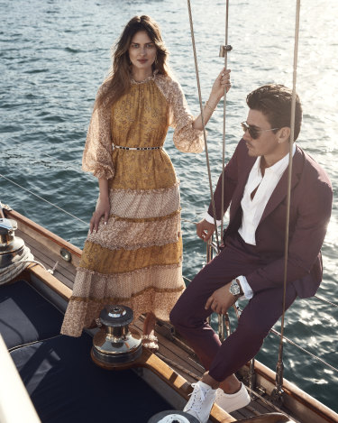 "She wears Tigerlily ""Emica"" maxi dress, $299; Zara slides, $90; David Yurman earrings and bracelets, from Fairfax & Roberts, as before. He wears BOSS suit jacket, $779, and trousers, $319; M.J. Bale ""Sidgwick"" Oxford shirt, $130; Longines ""HydroConquest"" watch, $2400; R.M. Williams ""Surry"" sneakers, $295; and Hugo Boss sunglasses, $264."