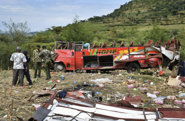 Kenyan police and other rescuers attend the scene of a bus crash near Kericho in western Kenya.