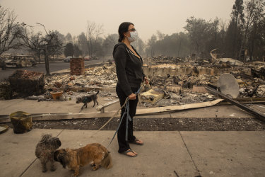 Lexi Sovllios from Talent, in Oregon, stands amid the ruins of her home.