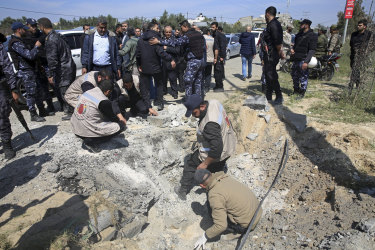 Hamas security services personnel inspect the site of the explosion.