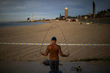 A man skips with a skipping rope next to a closed beach in Barcelona, Spain.