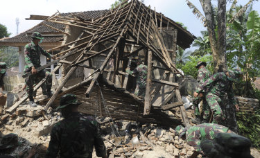 Indonesian soldiers remove debris from a house damaged by a strong earthquake.