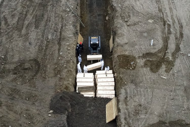 Workers wearing personal protective equipment bury bodies in a trench on Hart Island in the Bronx borough of New York.