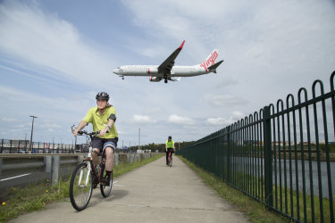 A Virgin Australia Boeing 737 flies over cyclists on the Alexandra Canal Cycleway near Sydney Airport.