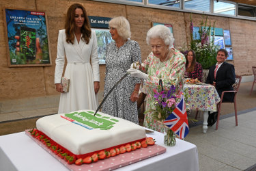 The Queen cuts a cake with a ceremonial sword.
