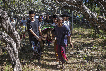 Men carry the body of a victim of last week's earthquake during a burial in Gangga, Lombok Island, Indonesia.
