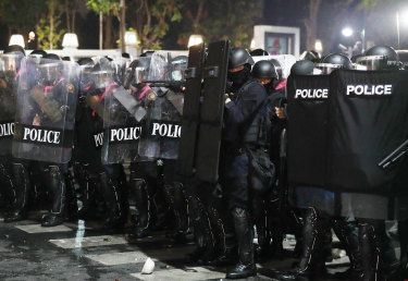 Riot police stand in formation preparing to disperse protesters.