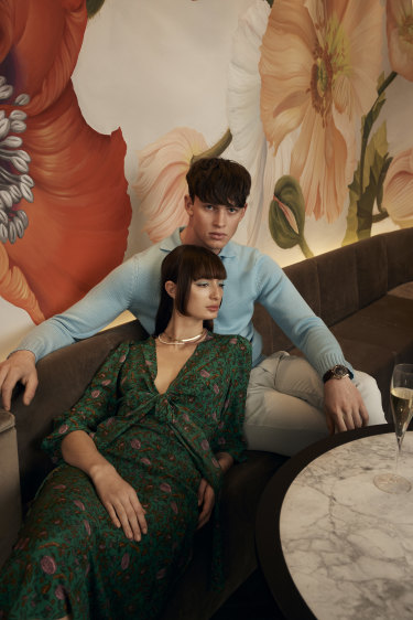 """Bela wears Scanlan Theodore dress, $850, and Arms of Eve """"Odette"""" necklace, $120, and """"Sophia"""" snake chain, $95. Zane wears Orlebar Brown top, $745, and pants, $350, and Omega watch, $17,675."""