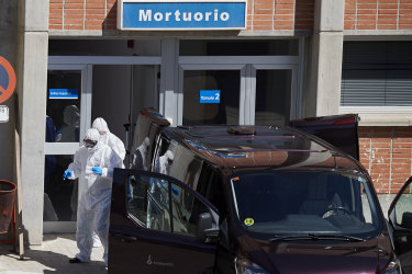 Workers transport a corpse from the mortuary of the Severo Ochoa Hospital on March 28, 2020 in Madrid, Spain.
