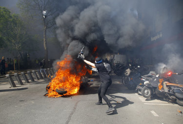 A protester throws a scooter onto a fire during a yellow vest protest in Paris.