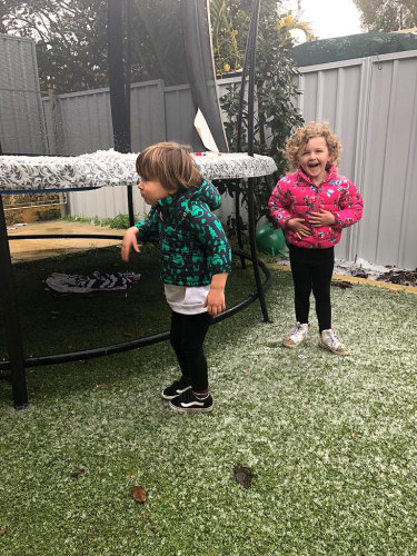 Little Nate and Coco enjoying the 'snow' in their Melville backyard.