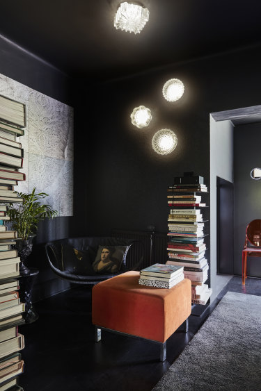 """In the intimate reading nook, a black leather """"Smock"""" chair by Patricia Urquiola sits beneath an artwork by Jennifer Jackson called Surfaces and Doubles."""