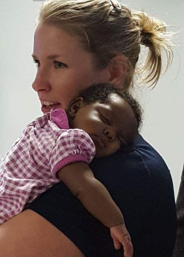 Michelle Burton comforts a baby after responding to a call in Alabama.