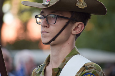 A young Army cadet stands guard next to his fellow cadets.