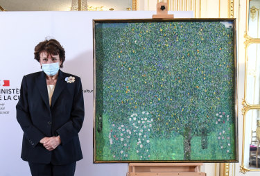"French Culture Roselyne Bachelot poses next to a spoiled oil painting by Gustav Klimt painted between in 1905 called ""Rosebushes under the Trees,"" during a ceremony at the Orsay museum in Paris."