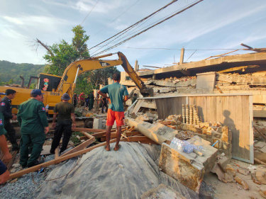 Heavy machinery removes debris after a building collapsed in Kep province.