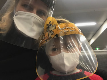 Astrid Magenau and son Hendrix wear a face mask and shield on-board their Qatar Airways flight from Germany to Sydney.