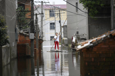 A woman pushes a makeshift raft down a flooded alleyway.