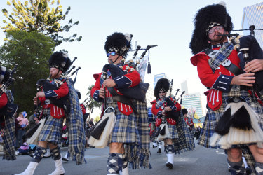 WA Police Pipe Band members play the bagpipe as they parade down St Georges Terrace.