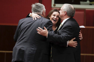 Crossbench senators Rex Patrick, Jacqui Lambie and Stirling Griff celebrate after the passage of the bill.