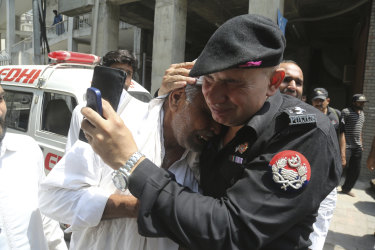 A police officer comforts a man who lost a relative in suicide bomb attack earlier this week.