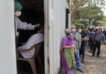 A health worker takes a nasal swab sample of a person to test for COVID-19 as others wait for their turn outside a field hospital in Mumbai.