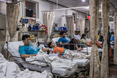 Patients who contracted the coronavirus lie in beds while connected to oxygen supplies in a  hospital in New Delhi.
