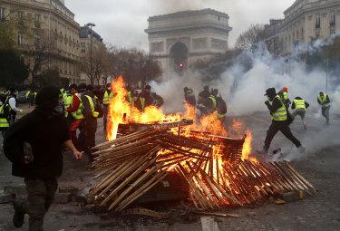 Demonstrators run by a burning fire near the Arc de Triomphe.