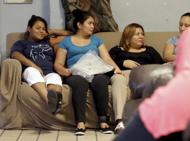 Carla, second from left, from El Salvador, holds a package containing batteries and accessories for her ankle monitoring bracelet as she socialises with other migrant mothers at the Annunciation House, El Paso, Texas.