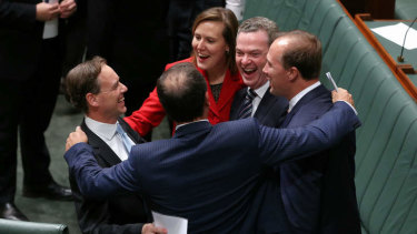 Then federal environment minister Greg Hunt is congratulated by colleagues after carbon tax repeal bills passed the lower House in 2014. Lowy's poll indicates support for the return of some form of price on greenhouse gas pollution.