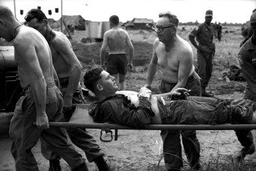 A 1st Battalion soldier, accompanied by Salvation Army Brigadier Aubrey Hall, is carried on a stretcher on June 26, 1965.