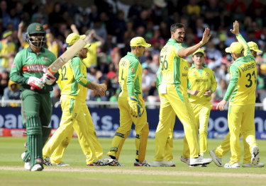Mitchell Starc, third right, celebrates with teammates after the dismissal of Bangladesh's Tamim Iqbal.