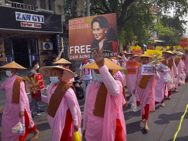Buddhist nuns display images of deposed Myanmar leader Aung San Suu Kyi during a street march in Mandalay.