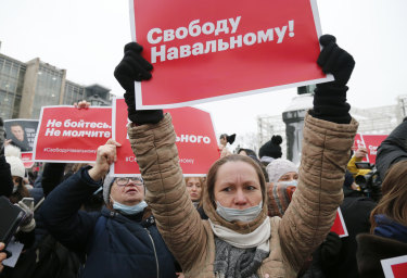 """Women hold placards that read: """"Freedom for Navalny!""""."""