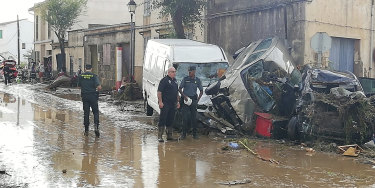Police officers stand next to vehicles destroyed in the flash floods.