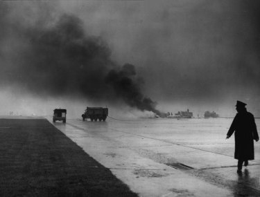 Smoke rises from the crash site of the Vulcan bomber at London Airport.