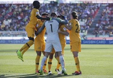Happy days: Socceroos teammates join Jamie Maclaren to celebrate his maiden international goal.